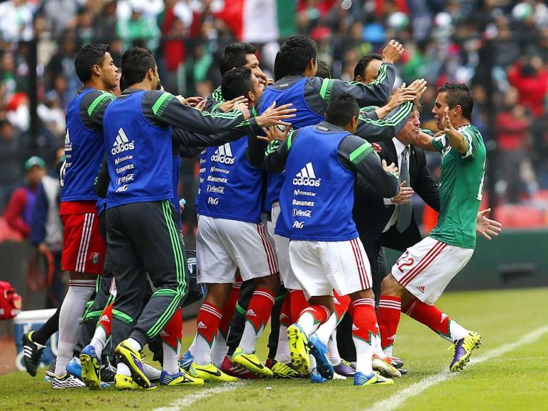 Mexico's Paul Aguilar, right, celebrates with team members after scoring his team's first goal during a 2014 World Cup playoff first round soccer match in Mexico City. (AP Photo)