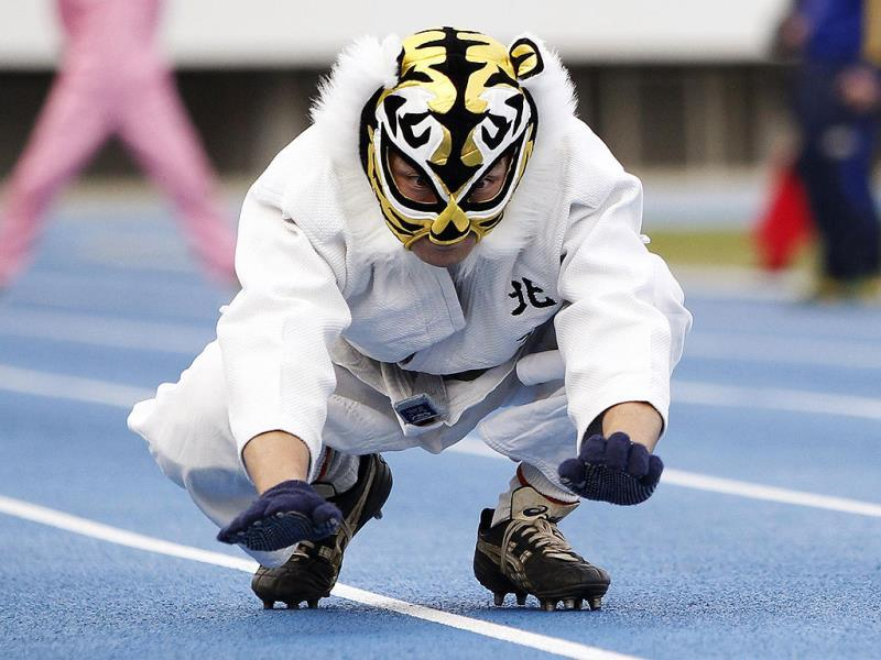Tatsuya Tanaka, a 47-year-old fish stall worker, participates in a 100-metre four legged race organized by Kenichi Ito, known as the