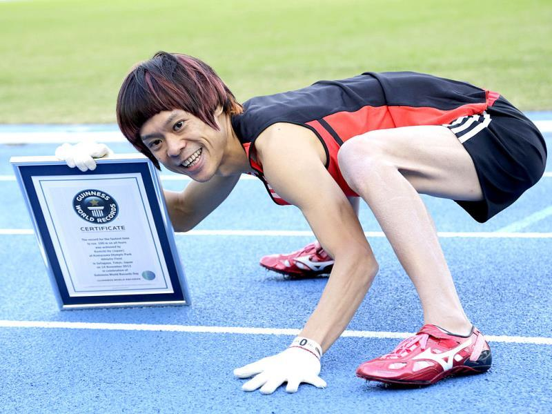Kenichi Ito poses for photographers with a Certificate of the Guinness World Records after setting the Guinness World Record fastest time for the 100-meter dash on his arms and legs on a race course at Komazawa Olympic Park Stadium in Tokyo. The 30-year-old Japanese finished in 16.87 seconds, shaving more than half a second off his 2012 run of 17.47. (AP Photo)