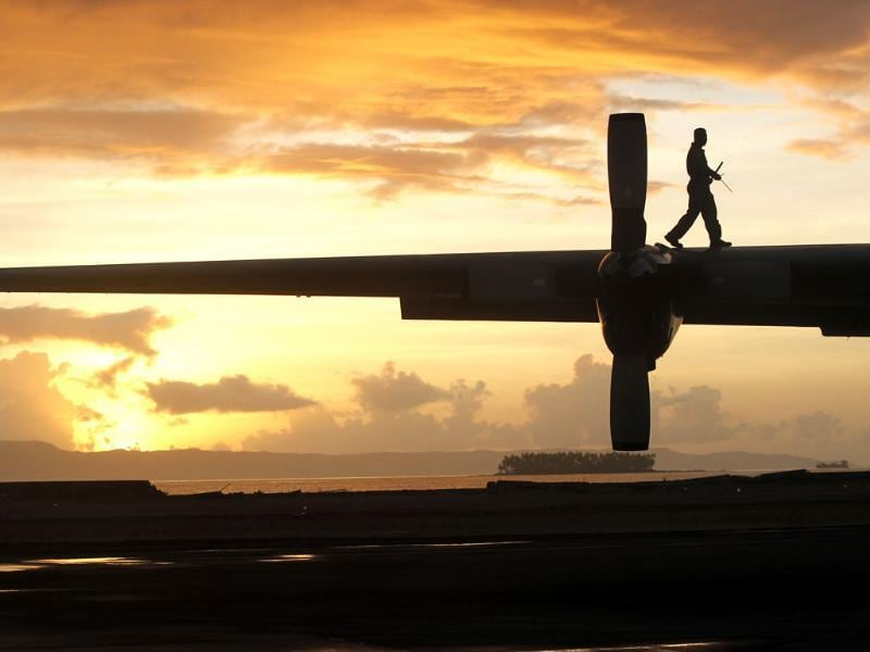 A Philippine air crew member does pre-flight checks on a C-130 evacuation flight at the airport in Tacloban, central Philippines. (AP Photo)