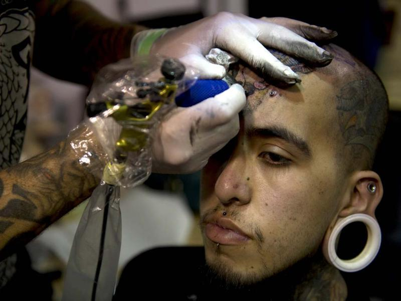 A man gets a tattoo at the Bogota Tattoo Convention, where, over 300 tattoo artists from around the world are showcasing their body art. (AFP Photo)