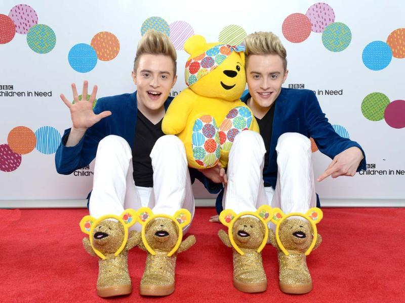 John and Edward Grimes, AKA Jedward, pose with Pudsey Bear backstage at the BBC Children in Need Appeal Show in London. (AP Photo)