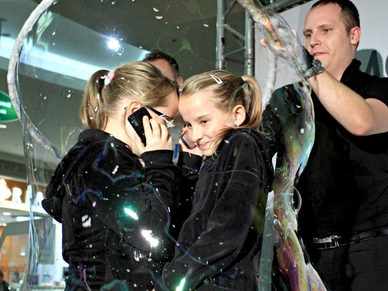 Two girls speas on the telephone from inside a giant bubble made by professional bubblemaker Matej Kodes (R) during the Guinness Book of records attempt to set a new record at a shopping mall in Olomouc, Czech Republic. (AFP photo)
