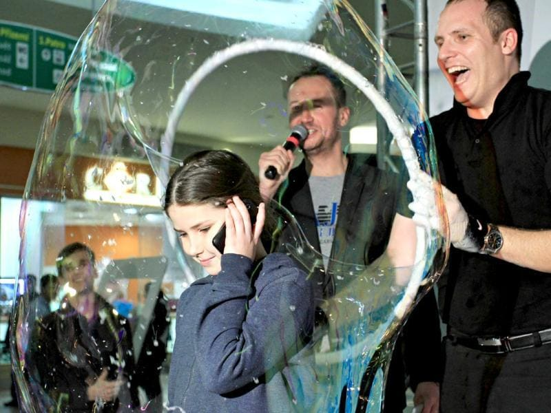 A girl speaks on the telephone from inside a giant bubble made by professional bubblemaker Matej Kodes (R) during the Guinness Book of records attempt to set a new record in Olomouc, Czech Republic. (AFP photo)
