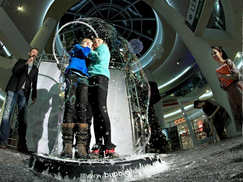 People speak on the telephone from inside a giant bubble made by professional bubblemaker Matej Kodes (R) during the Guinness Book of records attempt to set a new record in Olomouc, Czech Republic. (AFP photo)