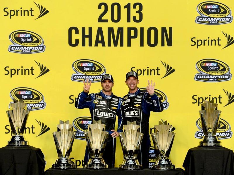 Jimmie Johnson (L), driver of the #48 Lowe's/Kobalt Tools Chevrolet, poses with his teams six trophies at the NASCAR Sprint Cup Series Ford EcoBoost 400 in Florida. (AFP Photo)