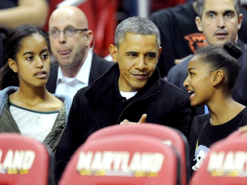 US President Barack Obama with his daughters Malia (L) and Sasha (R) in their seats before a college basketball in Maryland, US. (AFP)