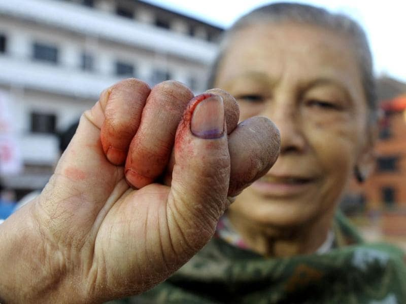 A Nepalese elder woman shows her finger after election official mark her finger with indelible ink at a polling station in Kathmandu. (AFP Photo)