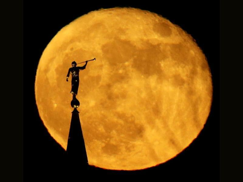 A statue of the Angel Moroni on top of a Latter-day Saints temple is silhouetted against the rising full moon in Kansas City. (AP Photo)