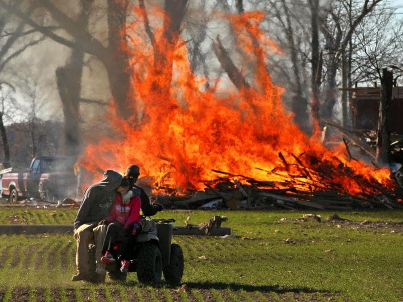 Residents of New Minden in Illinois, burn storm debris from a home destroyed in Sunday's tornado. (AP Photo)