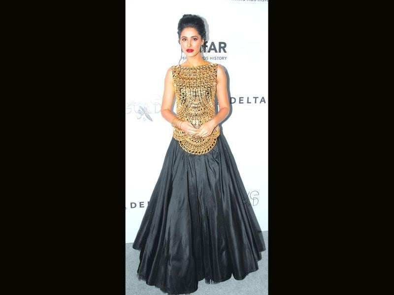 Nargis Fakhri looks stunning in a dress at the amfAR event.