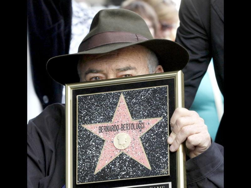 Italian director Bernardo Bertolucci holds a star plaque as he makes a rare visit to his star on the Hollywood Walk of Fame in Los Angeles. (AP Photo)