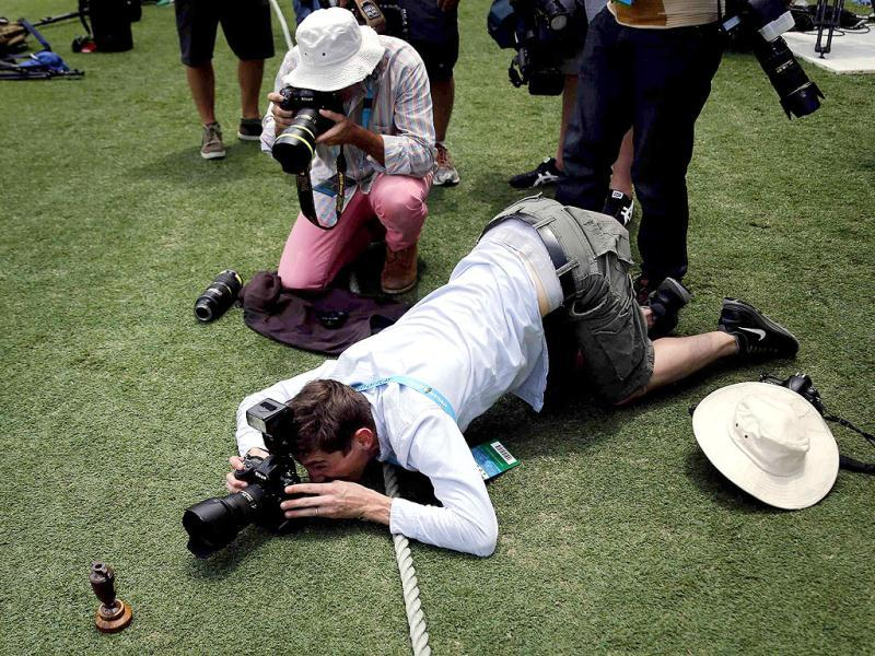 Photographers take pictures of a replica Ashes urn on the Gabba cricket ground in Brisbane. (Reuters Photo)