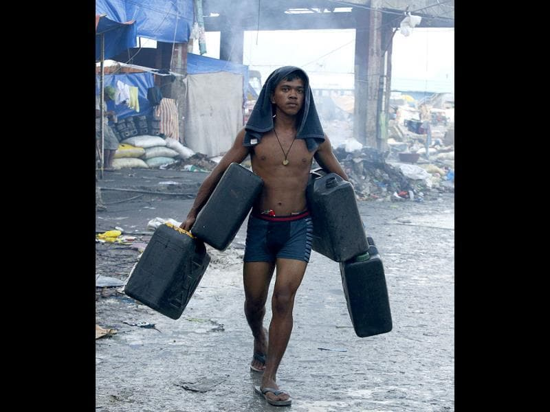 A typhoon survivor carries plastic containers to fetch water from a broken pipe after typhoon Haiyan battered Tacloban city nearly two weeks ago in central Philippines.  (Reuters)