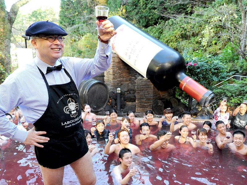 Bourgogne wine maker Laboure-Roi vice president Thibault Garin (2nd R) and sommelier Kensaku Ohara (R) pour the company's 2013 Beaujolais Nouveau wine into the wine spa at the Hakone Yunessun spa resort facilities in Hakone town, Kanagawa prefecture, some 100-kilometre west of Tokyo. As the new vintage Beaujolais Nouveau is officially uncorked, Hakone Yunessun started the annual 10-day-long Beaujolais Nouveau spa event with a guest of the wine maker's executive. (AFP PHOTO)