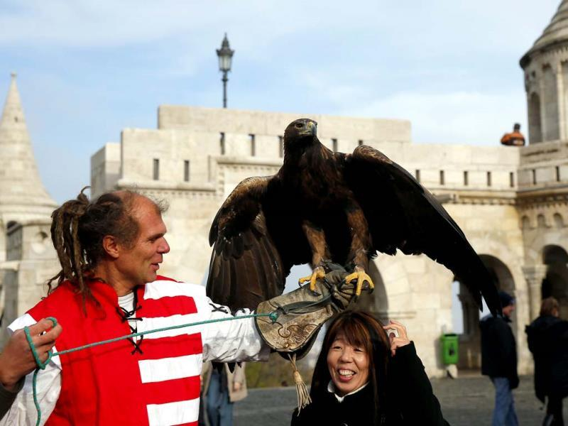 A eagle trainer entertains tourists in the Castle District in Budapest. (Reuters Photo)