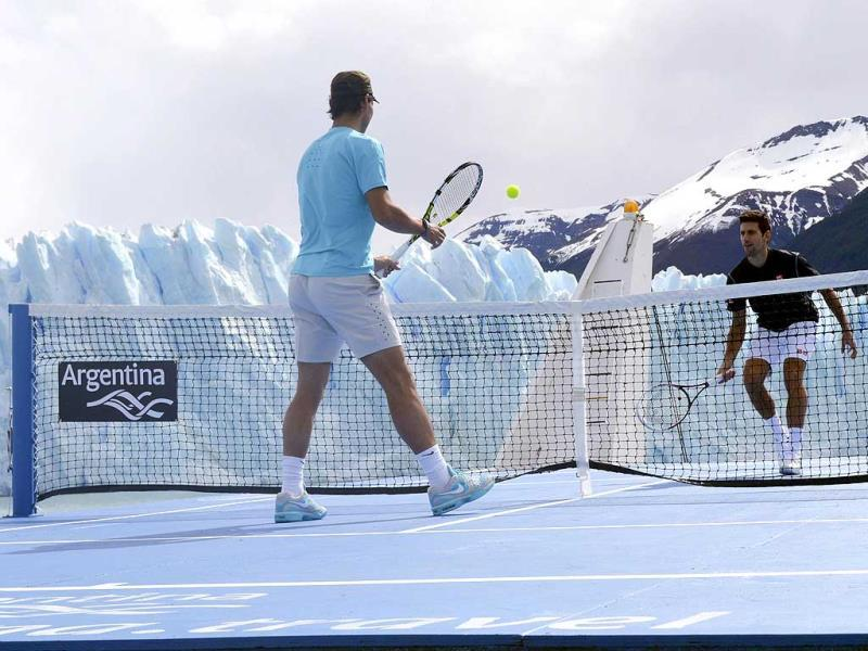 Novak Djokovic of Serbia and Rafael Nadal (L) of Spain play an exhibition tennis match on a court set up on the deck of the