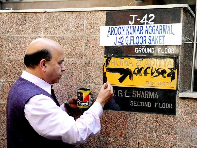 BJP leader Vijay Jolly writes 'accused' on the nameplate at residence of former managing editor of Tehelka magazine, Shoma Chaudhury in New Delhi. (HT photo)