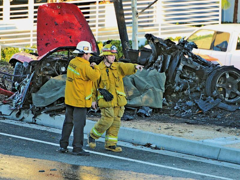 Sheriff's deputies near the wreckage of the Porsche that crashed into a light pole on Hercules Street near Kelly Johnson Parkway killing Paul Walker. (AP Photo)