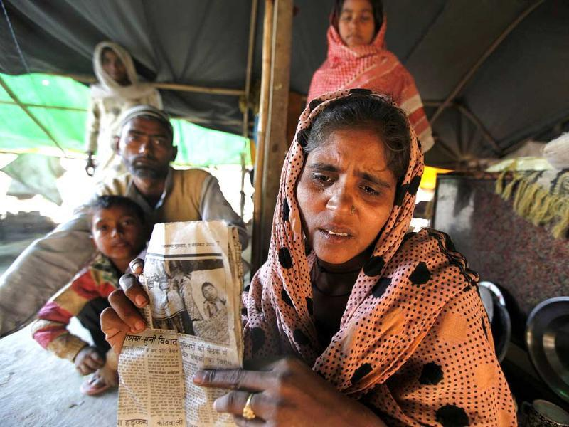 Shehnaaz, 34, and husband Mohd Shehzad, 38, show a local newspaper's cutting which carried the photo of their son who died because of dengue. (Raj K Raj/ HT Photo)
