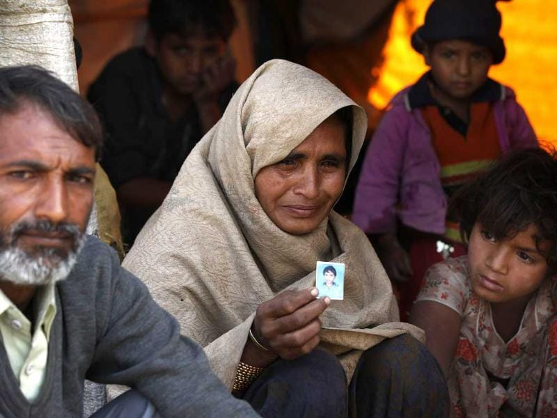 Nawab Ali, 38, with his wife Balkeesha, 34, show the photograph of their 11-year-old son who died due to cold after coming to the camp. (Raj k Raj/ HT Photo)