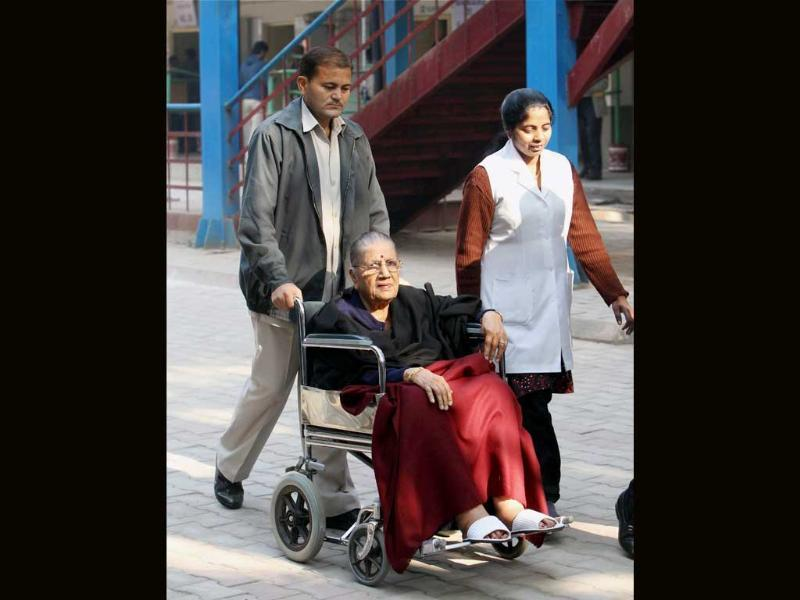 A patient in a wheelchair is taken to a polling station to vote during Delhi Assembly election in New Delhi. (PTI Photo)