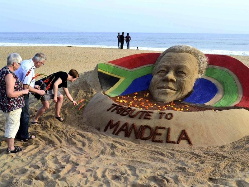 Tourists offer floral tributes near a sand sculpture of Nelson Mandela on a beach in Puri. (AP)