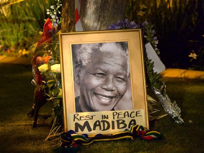 This picture shows a framed image of former South African president Nelson Mandela as people pay tributes following his death, in Johannesburg (AFP)