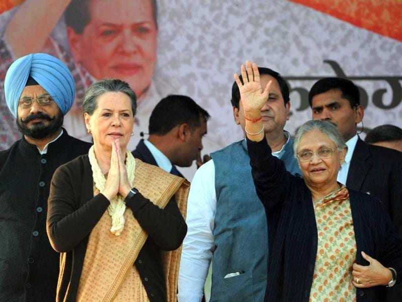 Congress president Sonia Gandhi (2nd L) and Delhi chief minister Sheila Dikshit (R) gesture and wave towards supporters during an election rally in New Delhi. (AFP)