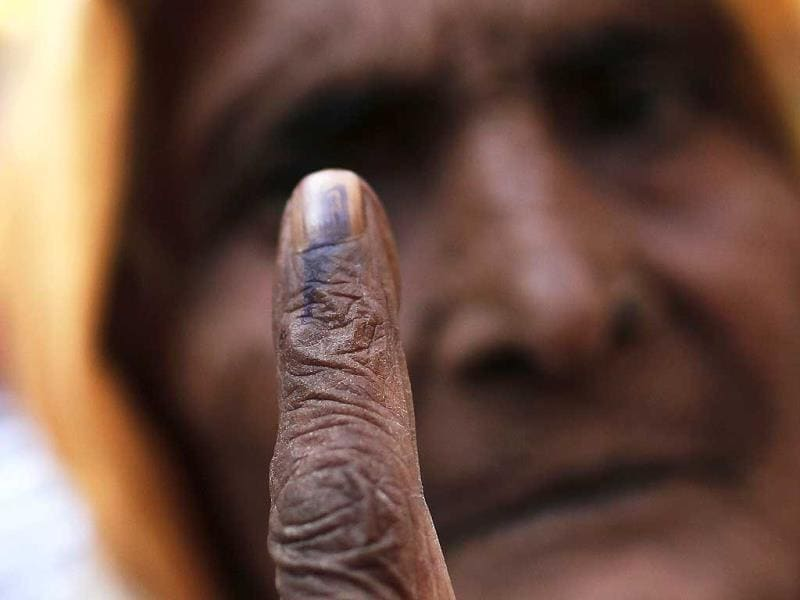 A woman shows her ink-marked finger after casting her vote at a polling station during the state assembly election in New Delhi. (Reuters)