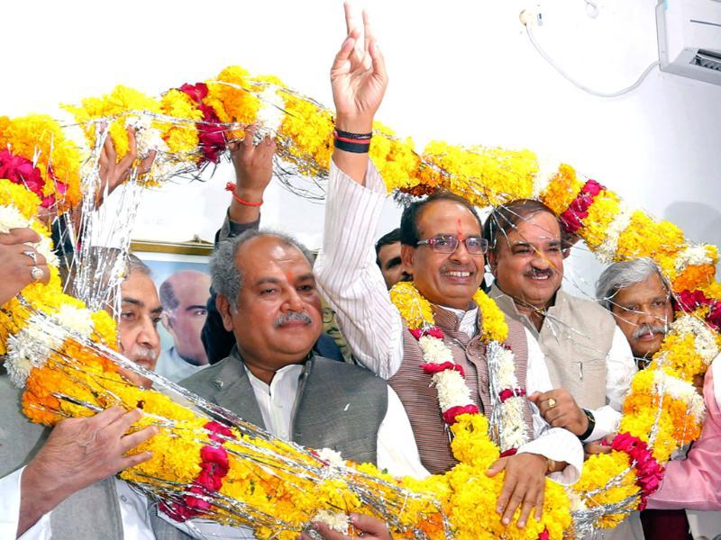 Shivraj Singh Chouhan being garlanded as his partymen celebrate the BJP's third consecutive victory in the state assembly elections in Bhopal. (AFP)