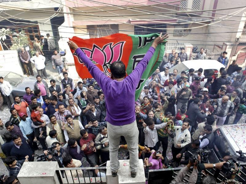 A man unfurls the BJP's flag as supporters celebrate the party's victory in the Delhi assembly elections. (AP)