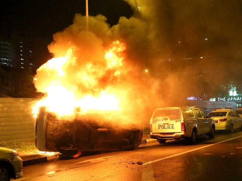 A police car (L) flipped on it side on fire after rioters went on a rampage in Singapore's Little India district. (AFP Photo)