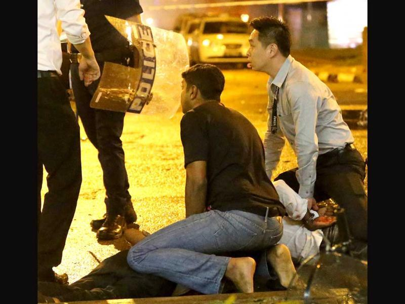 Two plainclothes policemen apprehending a man (bottom) after rioters went on a rampage in Singapore's Little India district. (AFP Photo)