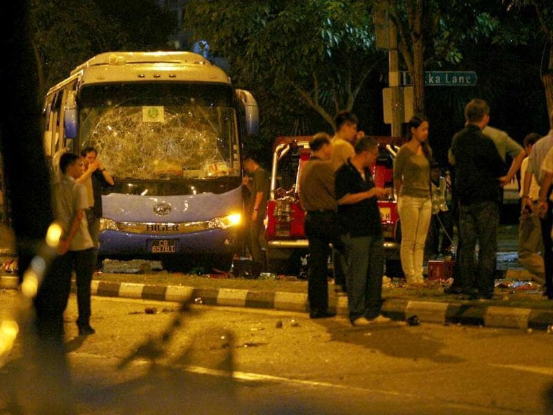 Officials stand around a bus with a smashed windshield following a riot in Singapore's Little India district. (Reuters)