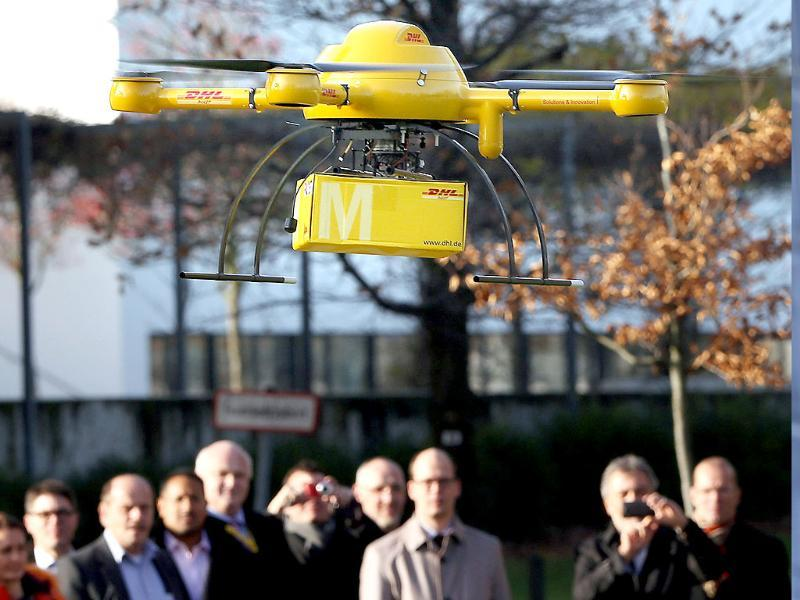 A drone with a small parcel flies in front of journalists in Bonn, Germany. (Reuters)