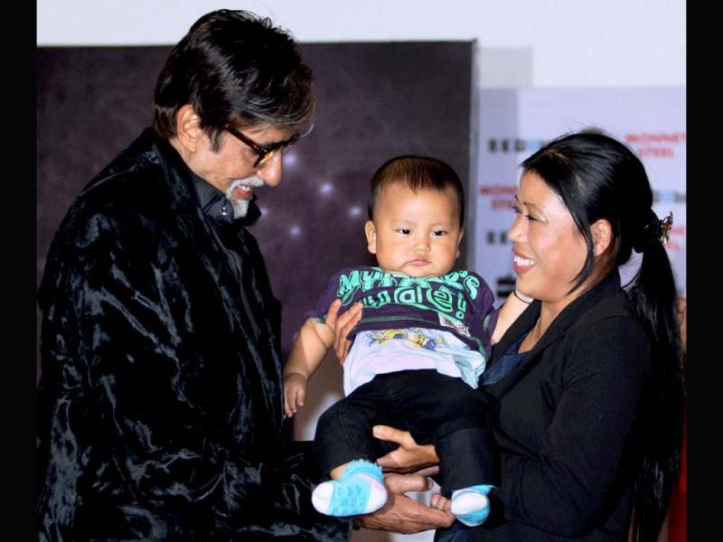 Amitabh Bachchan holds Mary Kom's little bundle of joy, as he launches her autobiography Unbreakable.