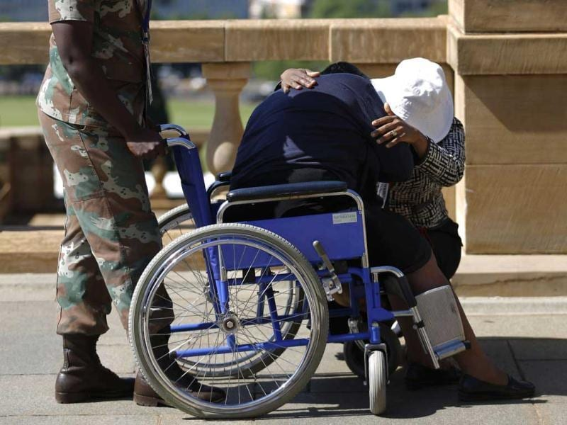 A woman in a wheelchair is comforted after paying her respects to former South African President Nelson Mandela during the lying in state at the Union Buildings in Pretoria, South Africa. (AP Photo)