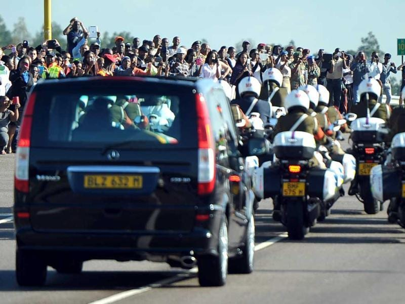 People celebrate as the funeral cortege of South African former president Nelson Mandela drives on its way to the Union Buildings after leaving the Military Hospital in Pretoria. (AFP Photo)
