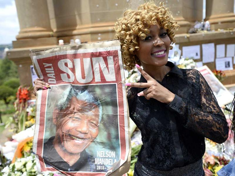 A woman holds a portrait of Nelson Mandela as people queue to bid farewell to the South African former president lying in state outside the Union Buildings in Pretoria. (AFP Photo)