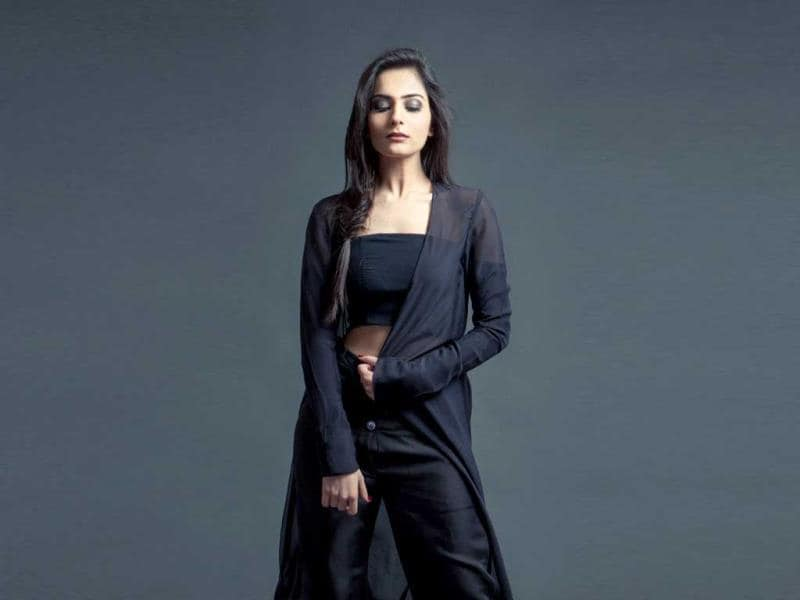 Surbhi Sethi, a blogger of HeadTilt, can be seen wearing a sheer black coat over a deconstructed black silk blouse and double waist-band trousers.