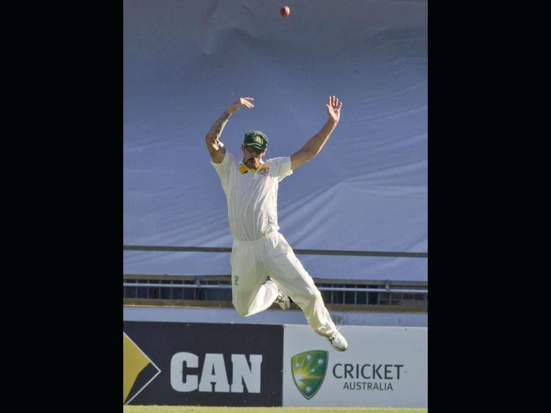 Australian fast bowler Mitchell Johnson taking a difficult catch to dismiss England's Kevin Pietersen on the second day of the third Ashes Test in Perth. (AFP Photo)