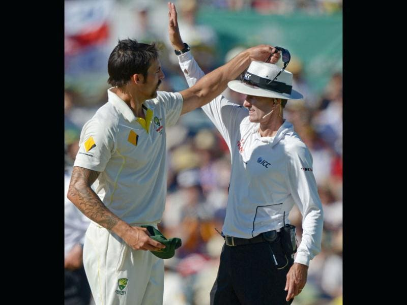 Australian bowler Mitchell Johnson (L) takes his sunglasses off umpire Billy Bowden (R) on day two of the third Ashes Test in Perth. (AFP Photo)