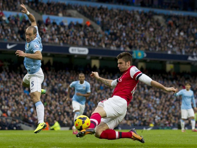 Arsenal's Olivier Giroud shoots wide past Manchester City's Pablo Zabaleta (L) during their English Premier League soccer match at the Etihad Stadium. (AP Photo)