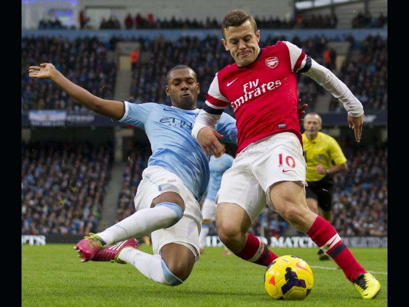Manchester City's Fernandinho (L) fights for the ball against Arsenal's Jack Wilshere during their English Premier League soccer match at the Etihad Stadium. (AP Photo)