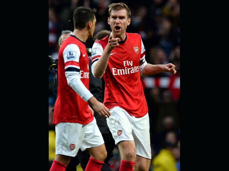 Arsenal's German defender Per Mertesacker (R) argues with German midfielder Mesut Ozil (L) after the final whistle of the English Premier League football match against Arsenal at the Etihad Stadium. (AFP Photo)