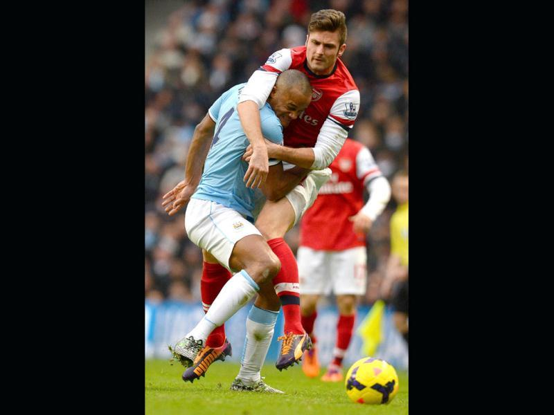 Arsenal's French striker Olivier Giroud (R) vies with Manchester City's Belgian midfielder Vincent Kompany (L) during their English Premier League at the Etihad Stadium in Manchester. (AFP Photo)