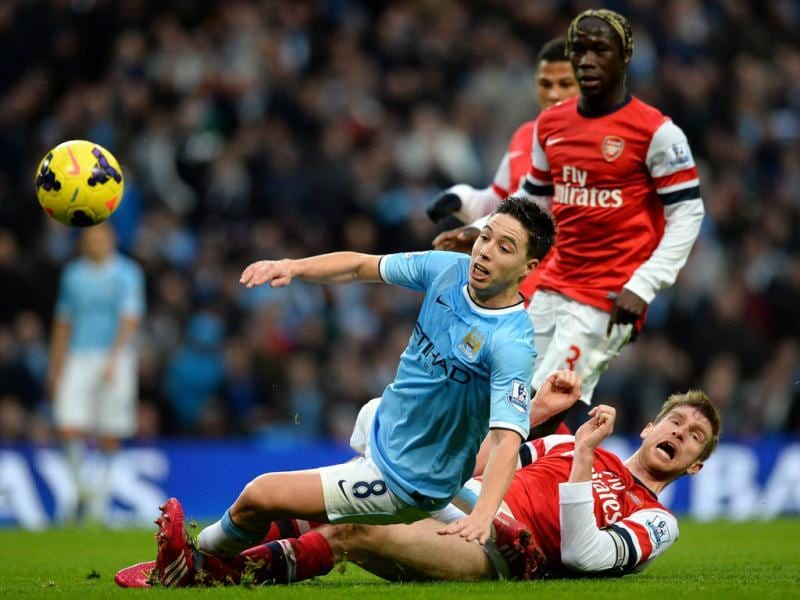 Arsenal's German defender Per Mertesacker (R) tackles Manchester City's French midfielder Samir Nasri (L) during their English Premier League football match at the Etihad Stadium in Manchester. (AFP Photo)