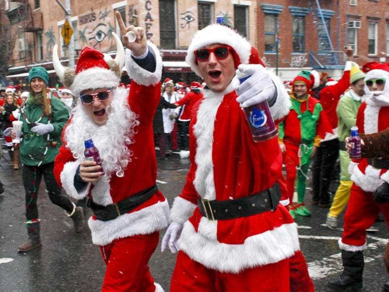 Revelers dressed as Santa Claus wearing Santa suits walk on the street during SantaCon in New York. (Reuters)