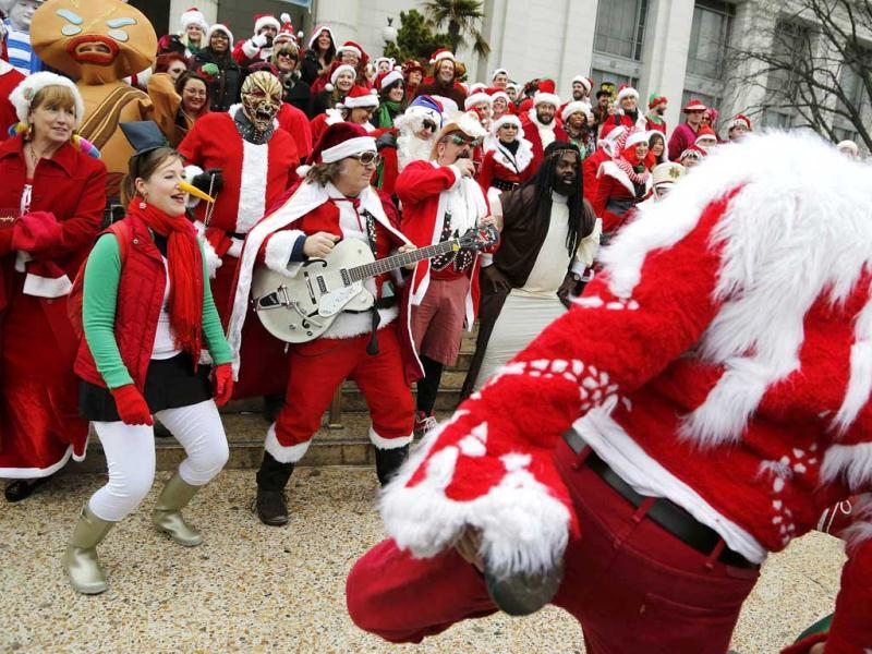 People dressed as Santa Claus stretch as they meet on the steps of the National Museum of Natural History in Washington. (Reuters)